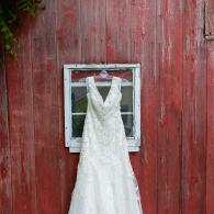 Crockette's Images Wedding Photography- Outdoor photo of the brides dress in front of a barn.