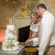 Crockette's Images Wedding Photography- Indoor wedding reception photo of bride and groom cutting th