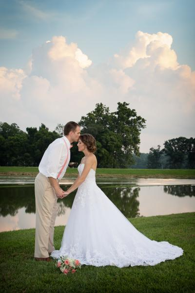 Crockette's Images Wedding Photography- Outdoor photo of bride and groom with a blue sky and clouds.]
