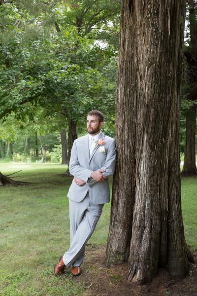 Crockette's Images Wedding Photography- Outdoor photo of a groom leaning against a tree.