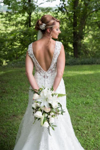 Crockette's Images Wedding Photography- Outdoor bridal photo with bouqet behind her back.