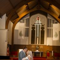 Crockette's Images Wedding Photography- Bride and groom kissing inside church.