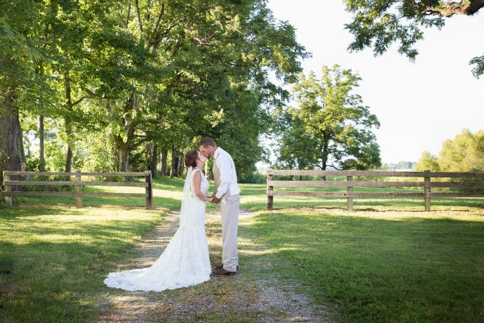 Crockette's Images Wedding Photography- Outdoor wedding photo of bride and groom kissing and holding