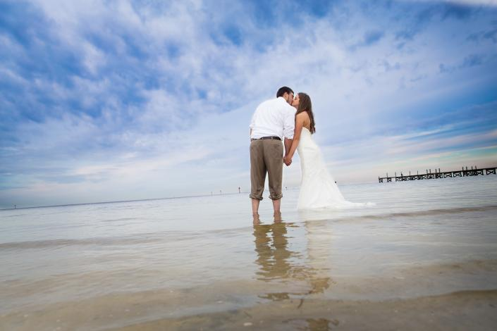 Crockette's Images Wedding Photography- Beach wedding photo with couple standing in the water.]