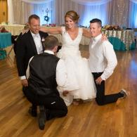 Crockette's Images Wedding Photography- Photo of the groom removing the bride's garter at indoor wed
