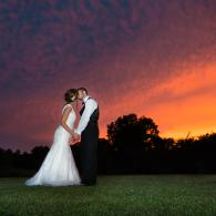 Crockette's Images Wedding Photography- Photo of bride and groom kissing in front of a colorful sky.