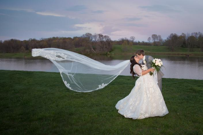 Crockette's Images Wedding Photography- Outdoor wedding photo of a bride and groom kissing, while he