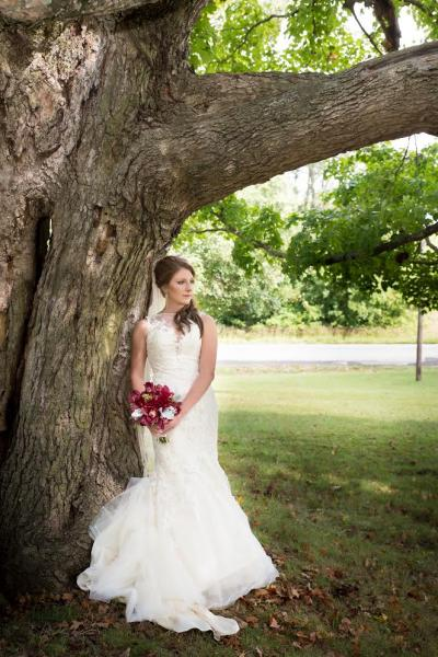 Crockette's Images Wedding Photography- Wedding photo of a bride standing agianst a tree.